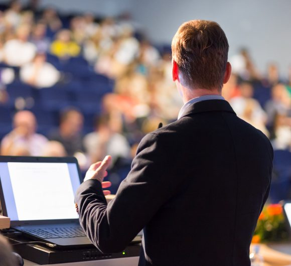 stock-photo-speaker-at-business-conference-with-public-presentations-audience-at-the-conference-hall-318208019